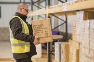 Crown Couriers warehouse assistant carrying box