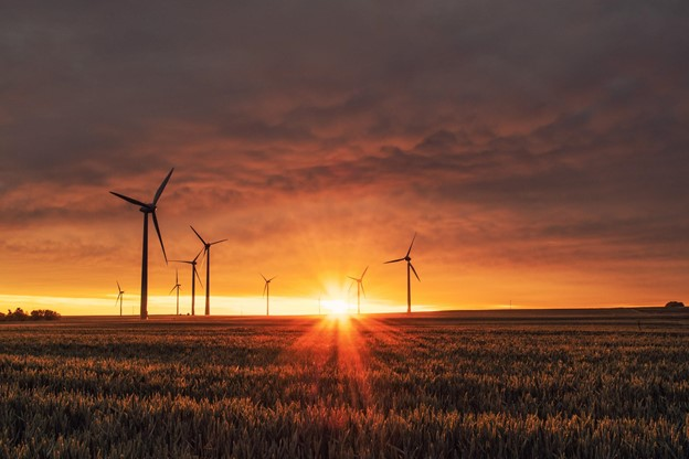wind turbines in a field with sunsetting behid for utilities courier service