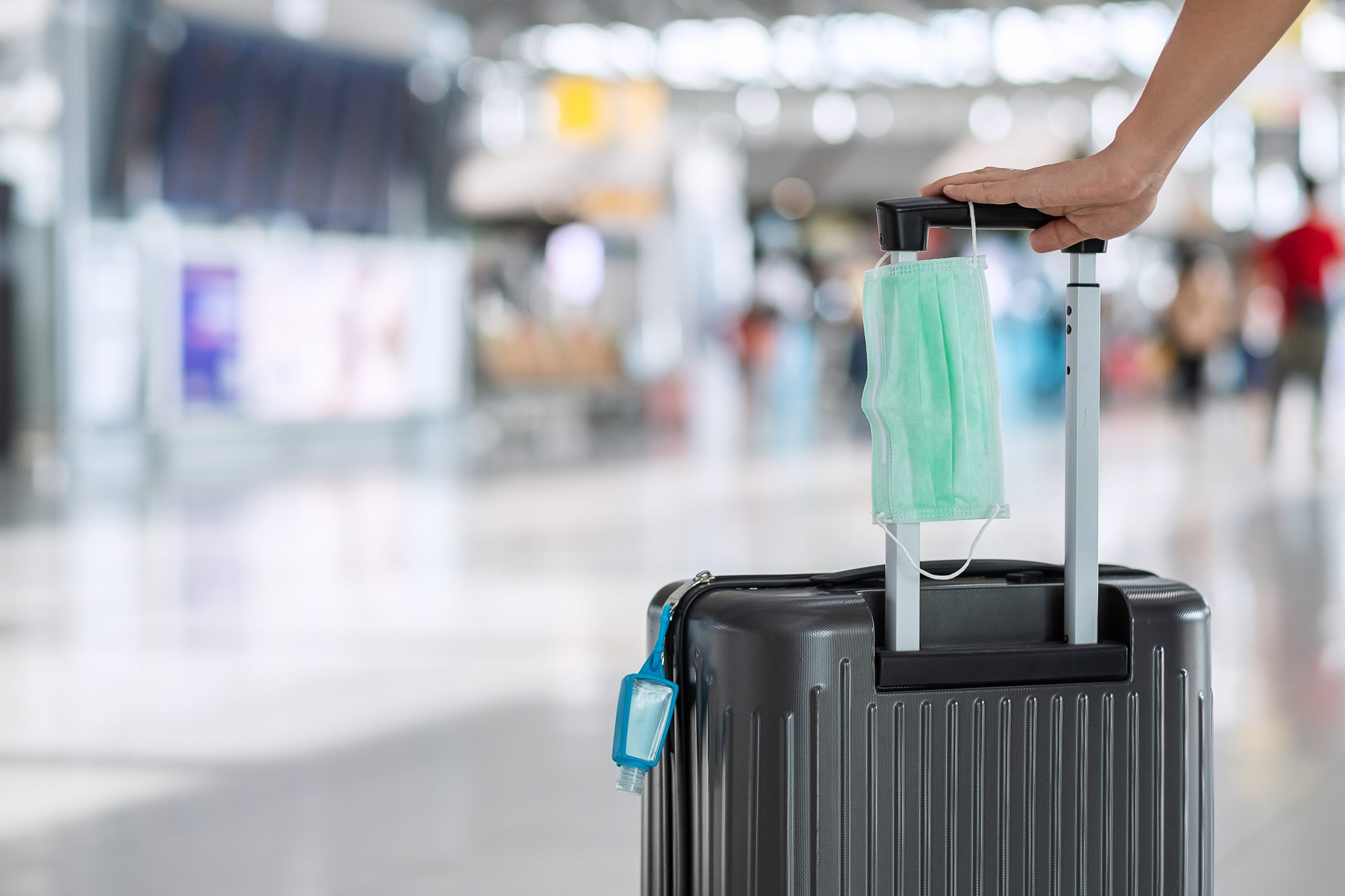 suitcase with medical mask showingresumption of travel during COVID restrictions
